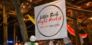 "a banner that says ""Little Rock Night Market,"" suspended above a crowd at Bernice Garden in Little Rock"
