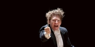Conductor Philip Mann at the podium, a fiery look on his face