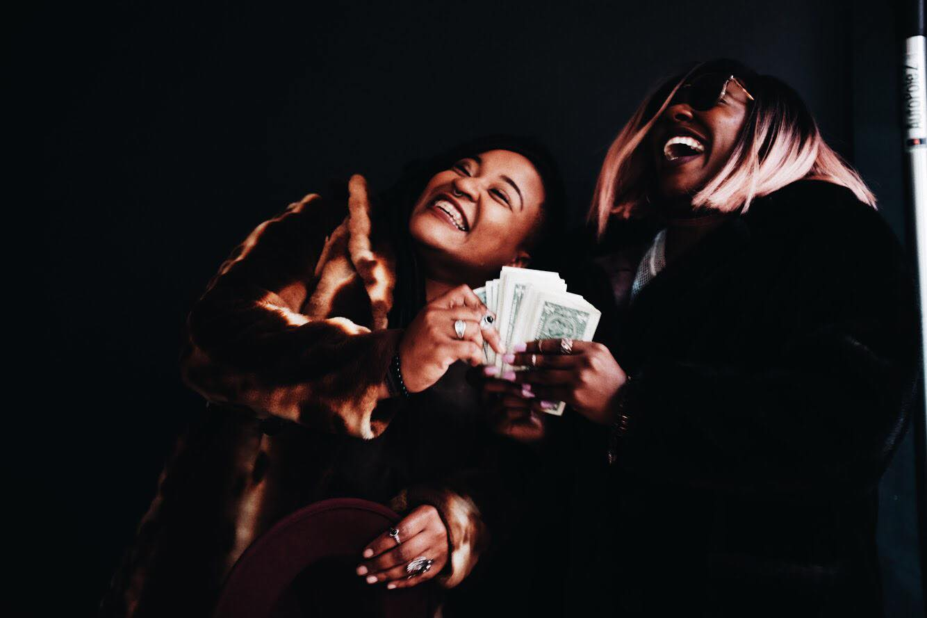 Dazzmin Murry and Brie Boyce laughing, clutching a fistful of dollar bills