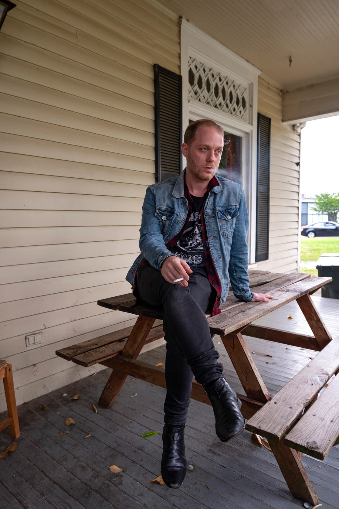 Picture of Arkansas director sitting on a picnic table and smoking a cigarette