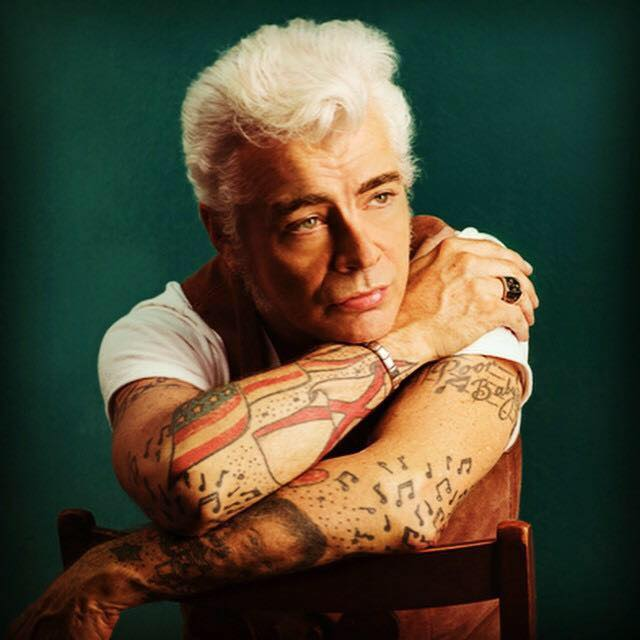 Dale Watson, seated backwards in a chair against teal backdrop