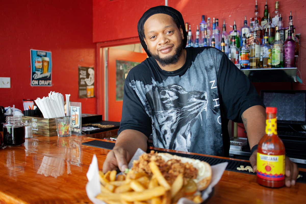 Picture of The Capital Seafood's Prince Williams holding a basket of fried fish and french fries