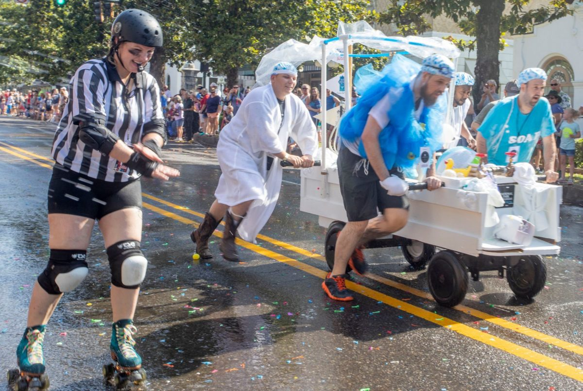 a referee running alongside a troupe of shower cap-clad contestants in Hot Springs' Running of the Tubs