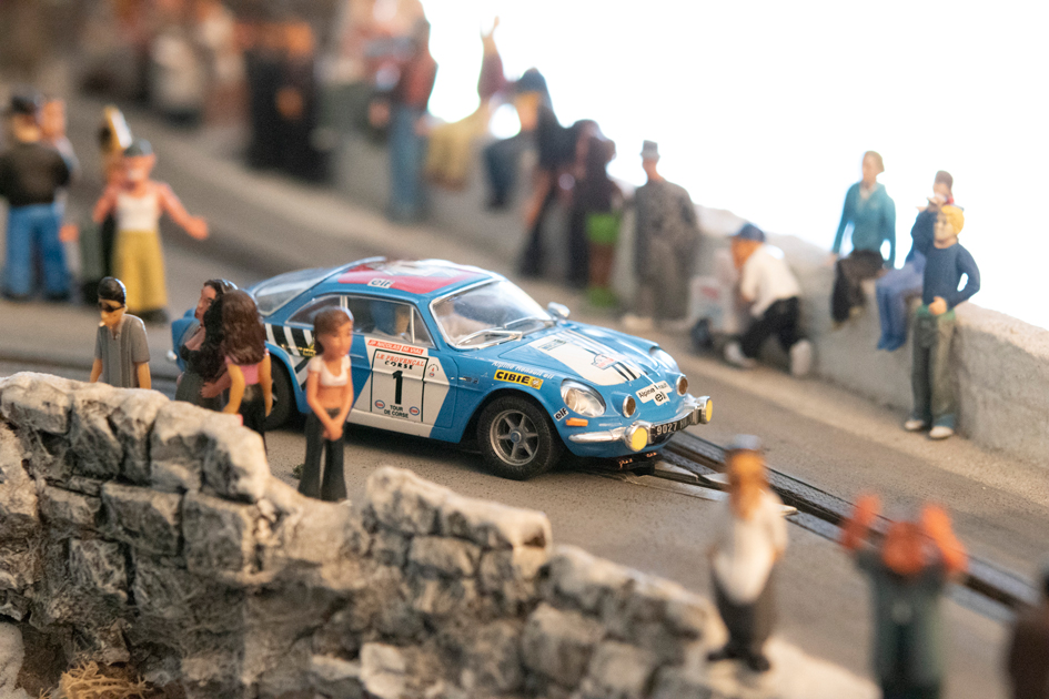 Detailed picture of model spectators surrounding a slot car on Jim Cunningham's slot car race track