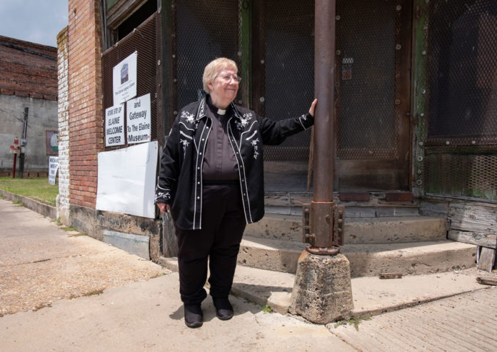 picture of Rev. Mary Olson standing in front of the future home of the Elaine Legacy Center